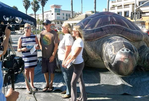 Denise Erkenoff of the Surfrider Foundation, Erik Helgesen of Environment California, Huntington Beach City Councilwoman Connie Boardman and Stephanie Barger of the Earth Resource Foundation address a TV camera at Huntington Beach Pier on Monday.