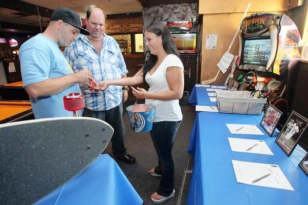 "Megan Hyde, right, sells raffle tickets to Michael David, left, and Rich Mishler at Suds Sports Grill in Huntington Beach on Friday. The fundraiser was held to help pay for three of her friends' medical bills who were wounded in the midnight screening of ""The Dark Knight"" in Aurora, Colo."