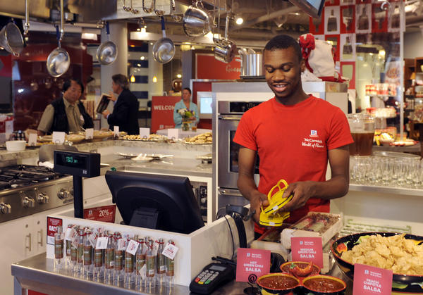 Nijah Bryant works behind one of the counters at the opening of the new McCormick World Of Flavors store at Harborplace.