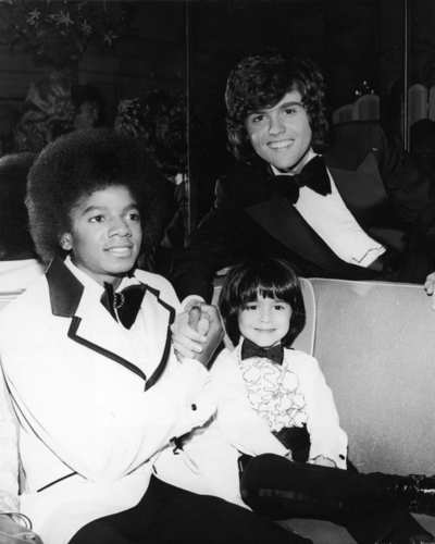 Michael Jackson in an oversized bow tie, left, and Donny Osmond pose with child actor Ricky Segall in 1974.