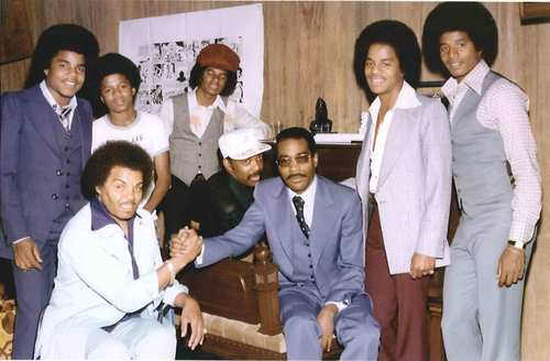 The Jacksons sign with producers Gamble & Huff in Philadelphia in 1976. Michael Jackson, in the back row, wears a hat and vest.