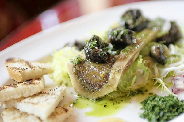 The roasted bone beef marrow, topped with garlic persillade escargot and served with toast points at Brasserie Pascal.