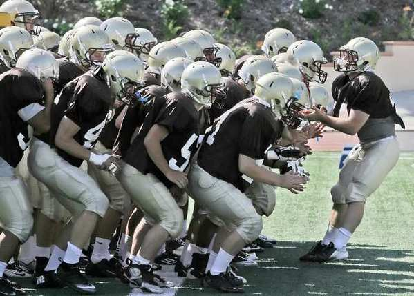 The St. Francis varsity football team congregates in the end zone to get fired up at preseason practice.