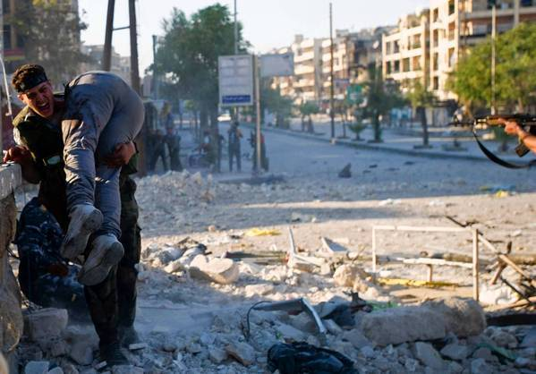 A Syrian rebel carries the body of his brother, killed during a battle in Syria's northern city of Aleppo.