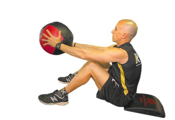Lying on a mat or a rug on your back, knees bent and feet flat on the floor, hold the medicine ball on your chest. Perform a sit up.