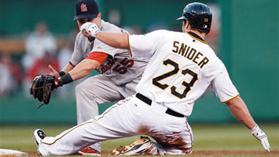 Pittsburgh Pirates' Travis Snider (23) slides into second with a double ahead of the tag by St. Louis Cardinals second baseman Skip Schumaker (55) in the first inning of a baseball game Wednesday in Pittsburgh.