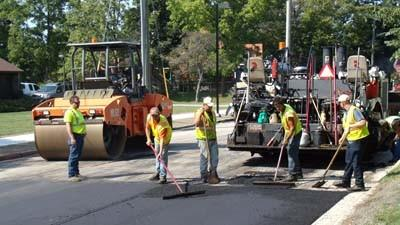 Workers tend to pavement installation Thursday along Howard Street near Sheridan Street in Petoskey.