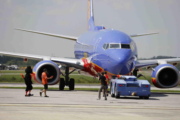 The Bird and pitcher Darren O'Day help marshal in a Southwest Airlines flight during a promotion at BWI.