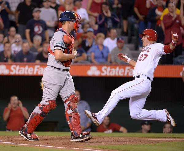 Los Angeles Angels center fielder Mike Trout (27) slides into home plate to score in the first inning as Boston Red Sox catcher Ryan Lavarnway (60) watches at Angel Stadium.