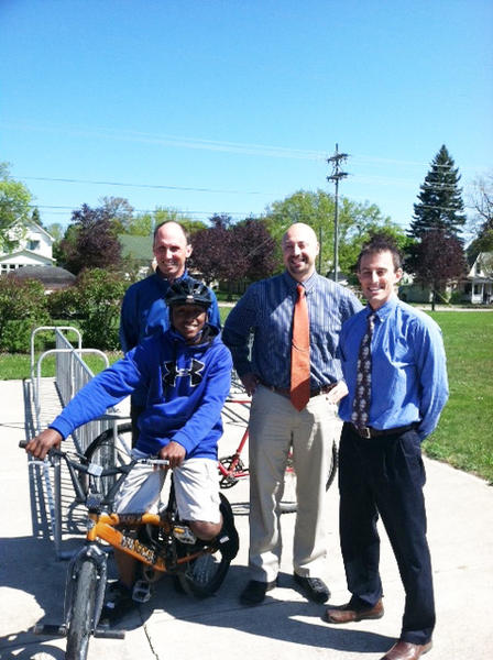Student Malcolm Williams, Safe Routes to School Coordinator Jim Harrington, Charlevoix Middle School teacher Brian Hawkins and principal Travis Garrett prepare to map potential bike routes for the Charlevoix Middle School. The Charlevoix County Community Foundation has funded the project.