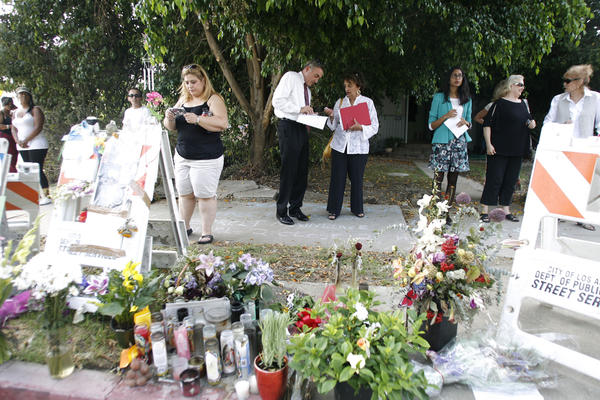 Families and friends of the victims of last week's electrocution accident attend a press conference where the accident happened on Ben Ave. and Magnolia Blvd. in Valley Village on August 22, 2012.