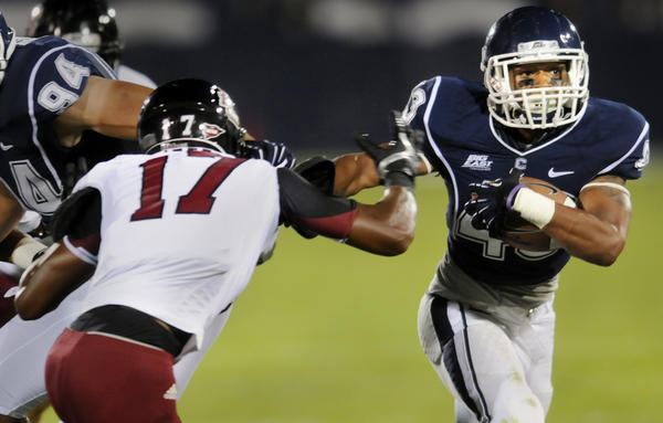 UConn's Lyle McCombs gains some yardage in the 2nd quarter against UMass defender Randall Jette (17). UConn football kicked off Thursday night against UMass at Rentschler Field.