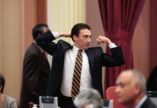 State Sen. Michael Rubio (D-East Bakersfield) stretches during a lull in Thursday's legislative deliberations in Sacramento. The lawmakers are facing a midnight Friday deadline to adjourn their two-year session.