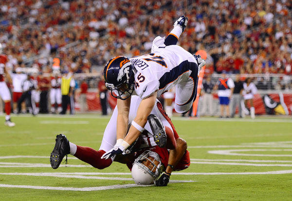 Arizona Cardinals wide receiver Michael Floyd flips over as he catches a touchdown pass under pressure from Denver Broncos safety Jim Leonhard in the second quarter during a preseason game at University of Phoenix Stadium.