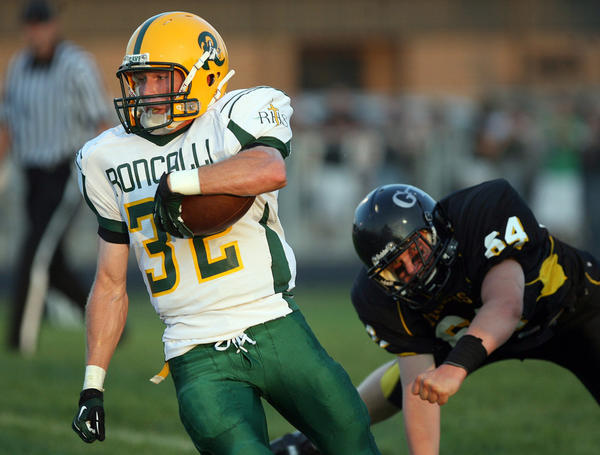 Aberdeen Roncalli's Matt Swallow, left, outruns the reach of Groton's Nick Dalchow, right, during Friday night's game at Doney Field in Groton. photo by john davis taken 8/24/2012