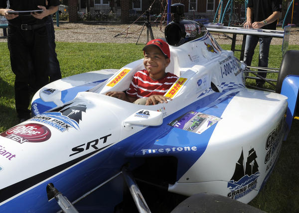 Isaiah Downs, 9, sits in an Indy car on the grounds of Kennedy Krieger School. Grand Prix driver Zach Veach is on left. Several drivers, along with a couple of cars from this weekend's race visited Kennedy Krieger School this morning.