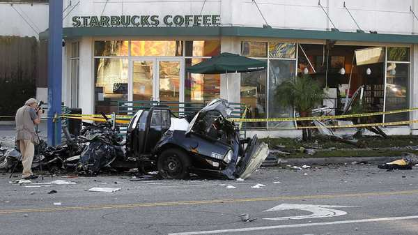 A police photographer documents the scene after a man driving a stolen LAPD cruiser smashed into a Starbucks on La Brea Avenue, officials said.