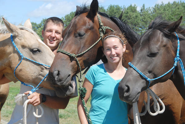 T.J. (left) and Jennifer Overly pose with their horses, (from left) Rowdy, Harley and Leroy, at their Atwood farm.