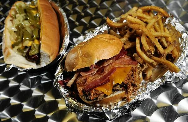 BBQ pork, beef brisket and bacon topped with cheddar cheese; and smoked sausage, peppers and onions on a split roll topped with American cheese are two sandwiches offered at the Rockhouse BBQ & Wings restaurant in Manchester.