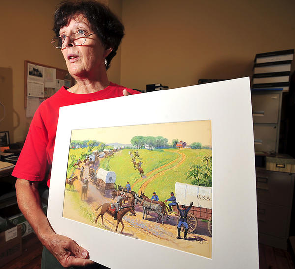 Vernell Doyle, president of Sharpsburg Historical Society, holds one of 51 watercolors by Garnet W. Jex. An exhibit of his work begins Friday, Sept. 7, at Washington County Arts Council in downtown Hagerstown.