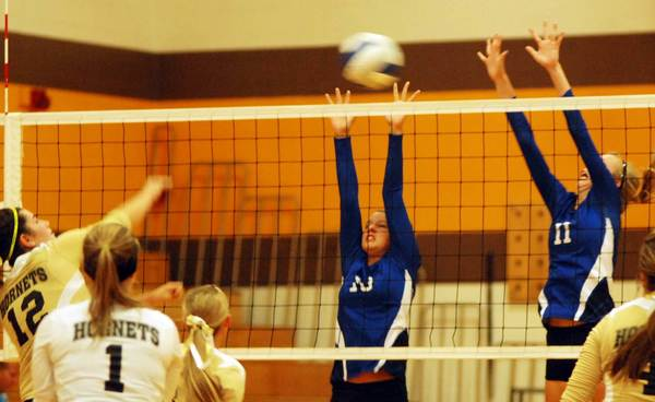 Pellston's Breah Carter (left) spikes the ball as Inland Lakes' Liz VanAlstine (middle) and Megan Skowronek (right) go up for the block Thursday during a Ski Valley Conference volleyball match at Pellston High School.