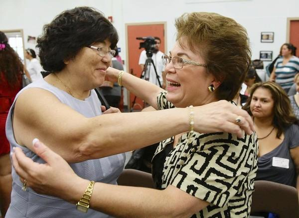 Kathy Onoye, left, executive director of elementary education for the Pasadena Unified School District, hugs Alice Petrossian of the Assn. of California School Administrators after the test results were released Friday.