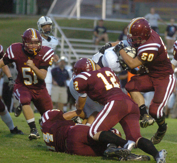 Garrard County's Bradley Rector (50), Dustin Keller (12) and Garrett Caudill (on ground) stop Lloyd Memorial quarterback Dexter Smith for a loss in the first quarter Friday. Garrard held Lloyd to 72 total yards in the Golden Lions' 35-14 win.