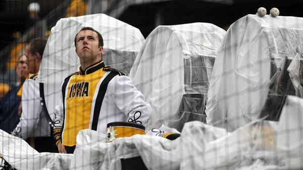 The Iowa Hawkeye marching band keeps its instruments covered up as it starts to rain before the Iowa football game against Northern Illinois today at Soldier Field. (Brian Cassella/Chicago Tribune)
