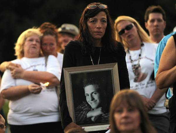 Felicia Miceli holds a photograph of her son Louie at a candlelight memorial for heroin victims Thursday on Roosevelt University's Schaumburg campus. It was a prelude to International Overdose Awareness Day, which was Friday.