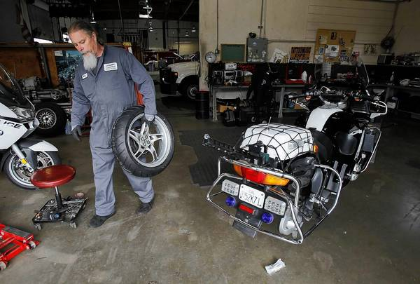 Costa Mesa city employee Billy Folsom works on a police department motorcycle in July.