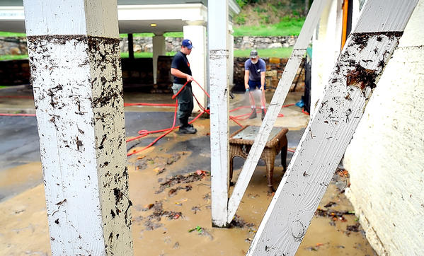 Preston Jamison, left, who works for Berkeley Springs State Park, and Terry Largent, chief operator of the Berkeley Springs Water Works Department, wash mud left by Saturday's flood off the sidewalks near the park's bath houses on Sunday. The water line from the flood can be seen on the white staircase supports in the foreground.