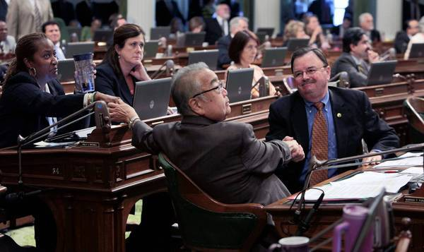 Assemblyman Warren Furutani (D-Gardena), center, receives congratulations from colleagues Holly Mitchell (D- Los Angeles) and Richard Gordon (D-Menlo Park) after his pension reform bill was approved by the Assembly on Friday.