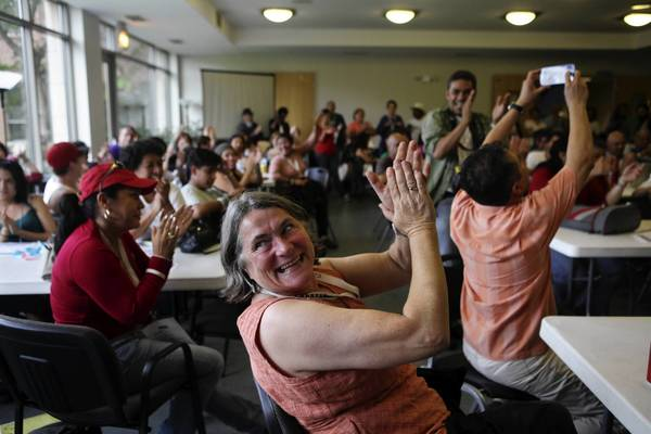 Kristen Muller, of San Francisco, claps with other participants of the Caravan for Peace as members are recognized Sunday for their contributions at the Augustana Lutheran Church in Chicago.
