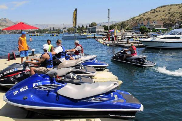 A survey found that among those who have taken vacations in the last 12 months, 25% stayed close to home to save money on vacations, down from 30% three years ago. Above, jet ski renters get some advice on Washington's Lake Chelan.