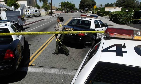 A Los Angeles County sheriff's deputy cordons off an area at Durfee Avenue and Michael Hunt Drive in South El Monte, where another deputy and a gunman traded fire Sunday morning.