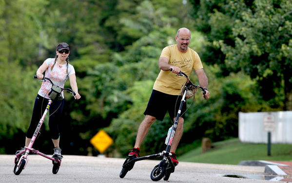 Heidi Shapiro and Fico Ferrer get some exercise Monday morning in Yorktown of  three wheeled Trikke scooter.
