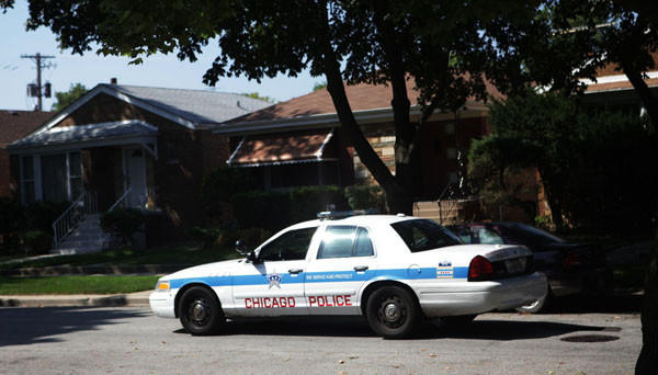 Members of the Chicago Police Department patrol the 9100 block of South Chappel Avenue where four people, including an 11-year-old girl, were shot at a family party on September 2, 2012.