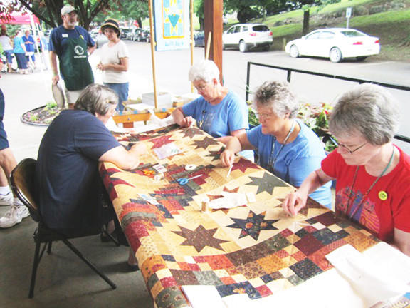 Quilters of the Piecemakers Quilt Guild of the Eastern Panhandle of West Virginia keep busy at the Labor Day picnic at Martinsburg's War Memorial Park. They are, from left, Jan Yates, Patsy Smith, Lucy Hoffman and Becky Roberts.
