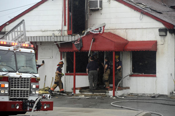 Firefighters look into the charred interior of Ross' Crab House, a long-time Dundalk restaurant that caught fire late Sunday night.