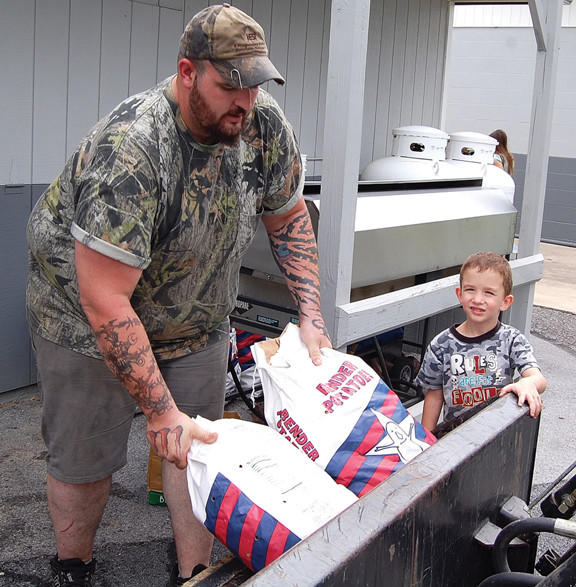 Paul Gerstenlauer Jr. of Greencastle, Pa., unloads sacks of potatoes for the Quincy (Pa.) Ox Roast on Monday. He was assistend by his 4-year-old son, Joshua.