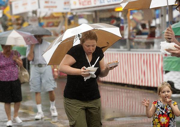 Courtney Guyer of Hoboken, N.J., juggles snacks while balancing an umbrella during Monday's downpour. She's with her niece, Gabrielle Guyer, 2, of Bryn Mawr.