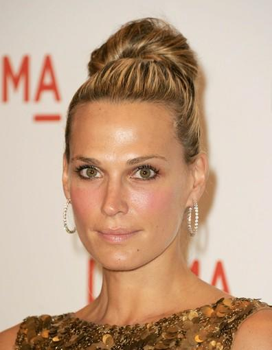 Molly Sims has her hair pulled all the way to the top of her head, piled up and coiled around itself like a dollop of whipped cream.