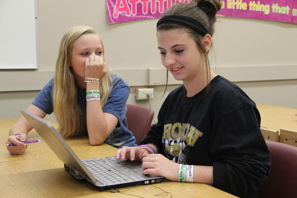 Willow Seurer waits for her friend Kayla Fordham to finish the days assignment. Sophomores, juniors and seniors at Groton High School are given convertible laptop computers that can be used as tablets.