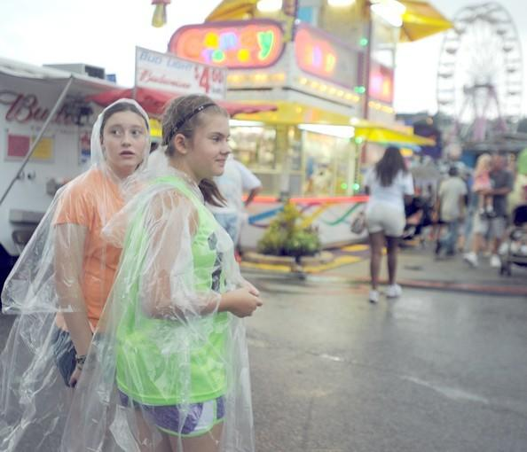 Jesse Whitehead, 12, of Jessup, left, and Marcy Marc, 12, of Elkridge, walk out into the midway between storms at the Maryland State Fair. High humidity and heavy rains marked much of the fair.