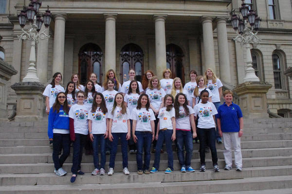 Members of the Little Traverse Youth Choir pose on the steps of the state Capitol building in Lansing while on a tour this spring. Heather Marvin (right) is the director of the choir.