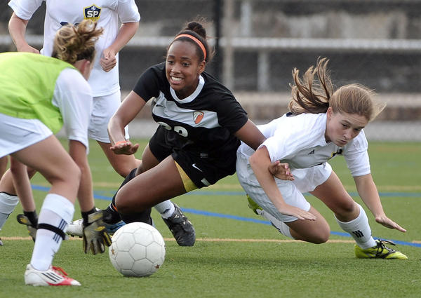 Substitute goalkeeper Maeve Murphy, Severna Park, picks up the ball as #22 Kyla Clark, McDonogh, and #17 Sydney Downing, Severna Park, go down. McDonogh vs. Severna Park in the AACC Pioneer Girls Soccer Tournament.