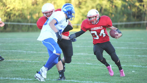 Senior back Dillion Kibby uses a block by Dakota Finnerty to spring free during the Cardinals' 34-28 loss to Inland Lakes Friday.