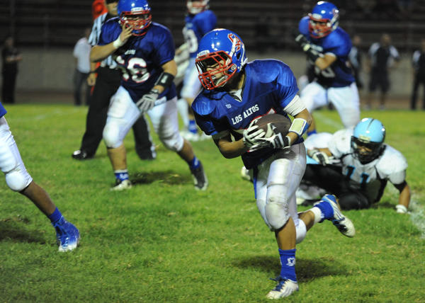 Estuardo Marcos runs the ball against Salesian.