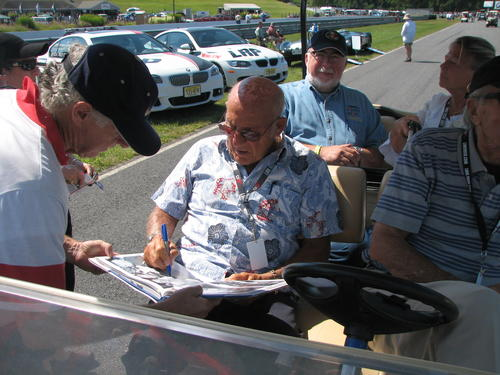 Racing legend Stirling Moss signs autographs at the event. Several of Moss's race cars were on display.