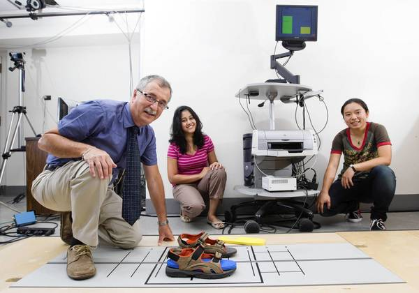 University of Illinois at Chicago physical therapy professor Alexander Aruin, from left, with Ph.D. candidate Neeta Kanekar and post-doctoral fellow Yun-Ju Lee test shoe inserts on a dual force platform that measures weight distribution between the right and left leg.